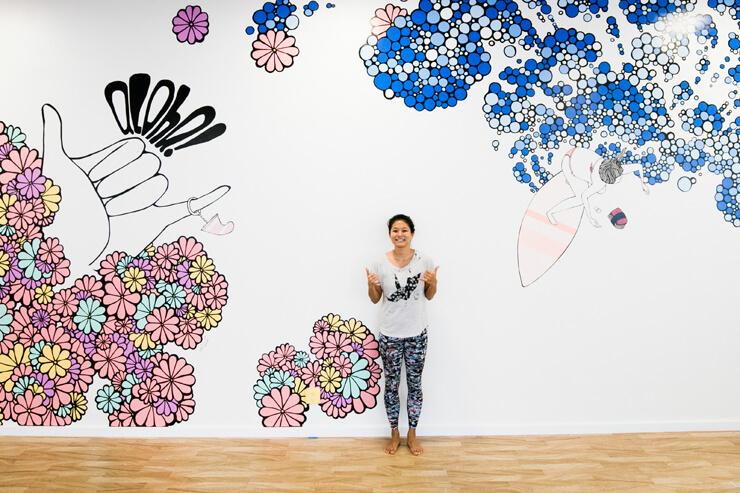 ハワイのアーティストKris Gotoが描いたウォールアートの前で